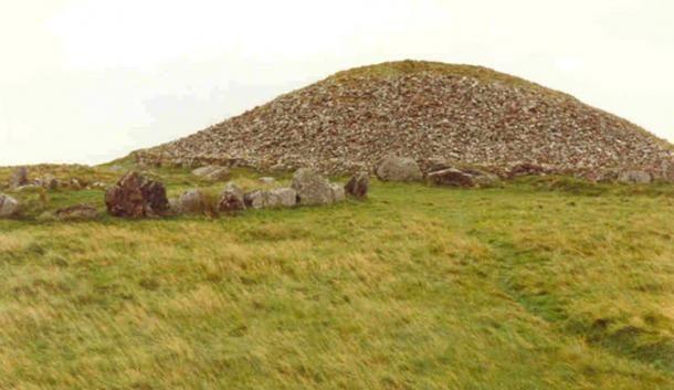"""Meath megyében lévő Loughcrew mealit sírjai Slieve na Calliagh (a Vén Banya hegy, ami Cailleach-ra utal) tetején találhatók, és magába foglalja a """"banya székeként"""" ismert peremkövet is. Slieve na Calliagh-n Cairn T egy klasszikus átjárós sír, amelyben a napéjegyenlőség napfelkeltéjének a sugara lehatol az átjárón és megvilágítja a megalitikus kővésetekkel teli belső kamrát. (Wikimedia Commons)"""
